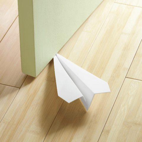 avión de papel como tope de puertas